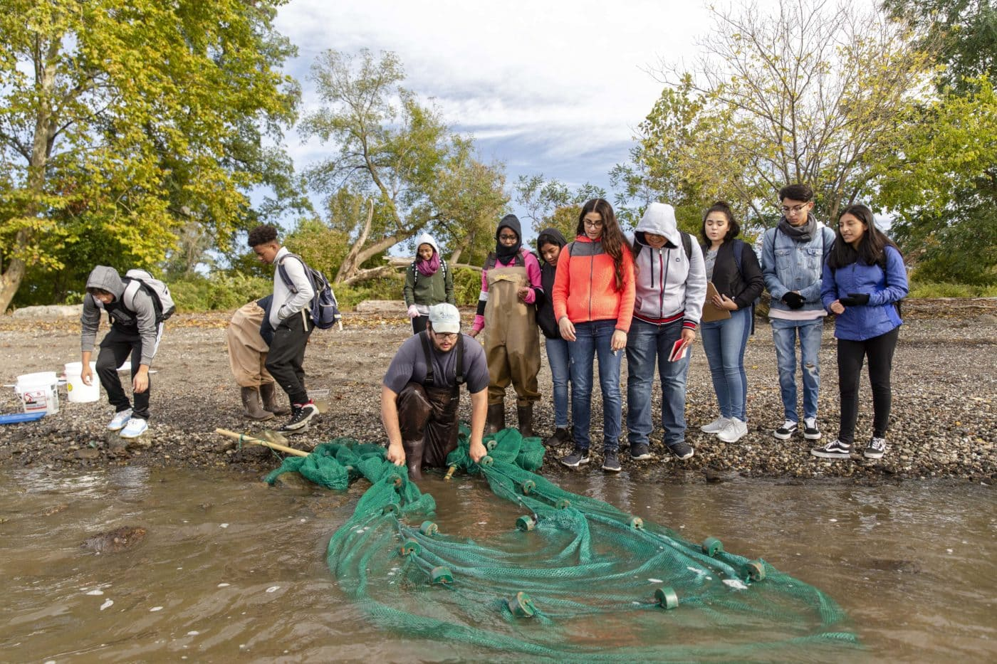 Teens seining for river creatures.